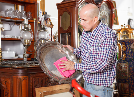 gentleman working in antique store carefully wiping dust on ancient items Stock fotó