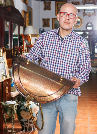 serious  mature man visiting shop of antique goods in search of interesting objects
