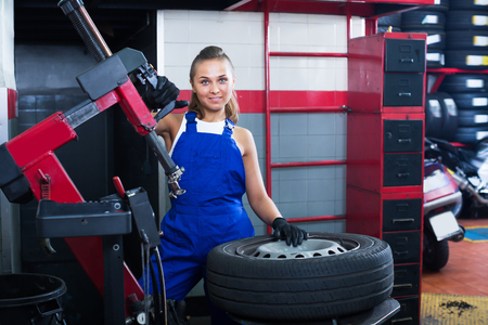 Happy woman technician standing with wheel at auto workshop