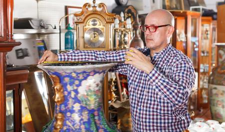 Interested elderly man measuring vintage amphora in shop of antique goods