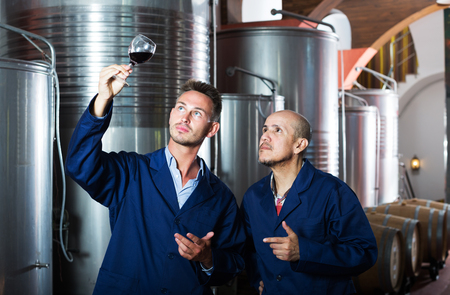 two poitive winery male workers in uniform holding wine sample 