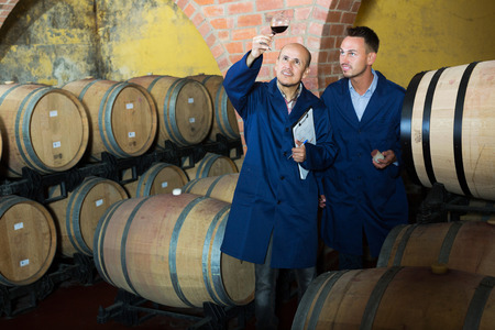 two winery employees wearing coats checking up wine sample in glass in aging section on winery manufactory Reklamní fotografie