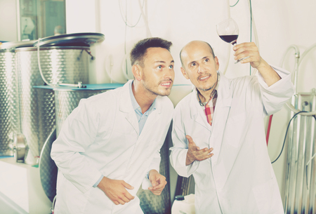 Happy two factory workers in uniform standing together and examining the sample of wine in the glass. Focus on young man