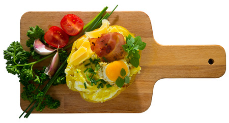 Top view of baked potatoes served on wooden board with fried egg, bacon, cheese, garnished with fresh scallions. Isolated over white background
