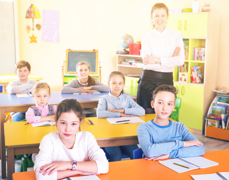 Portrait of diligent schoolkids with young female teacher during lesson in classroom Stock Photo