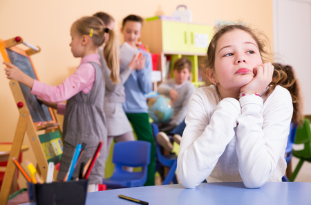 Sad bored schoolgirl sitting separately in classroom in break between lessons 写真素材