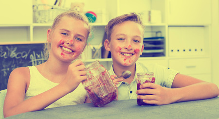 Portrait of sister with brother who are eating jam at time lunch at home. Banque d'images - 112584621