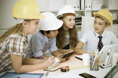 Group of children in helmet talking about building near laptop