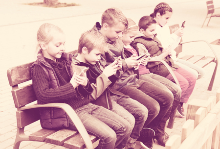 Group of children posing at urban street with mobile phones