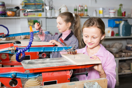 Capable of schoolgirls do wood carving during a lesson in applied arts