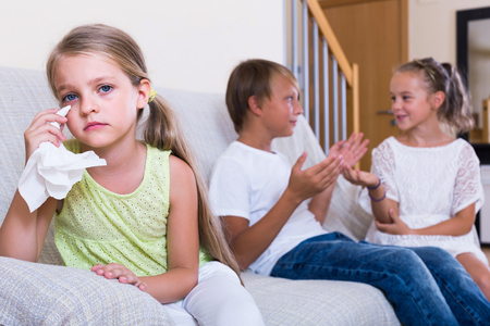 First amorousness: offended girl and couple of kids apart indoors