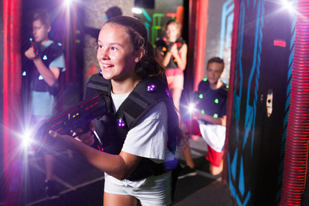 Emotional teen girl with laser pistol playing laser tag with friends on dark labyrinth