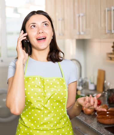 Positive girl housewife in apron  talking by phone  at home kitchen