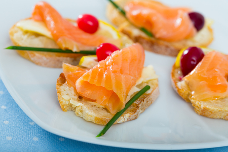 Tasty bruschetta with salmon, lemon, cranberry and green onion