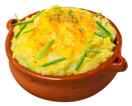 Potato gratin with whipped eggs and cheese served in clay pot. Isolated over white background Standard-Bild