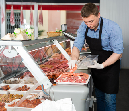 Skillful butcher working behind counter in butchery