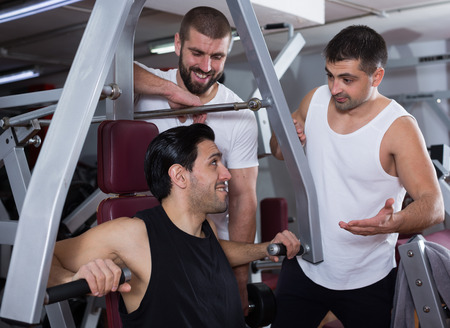 Portrait of three positive athletic male friends in modern gym 免版税图像