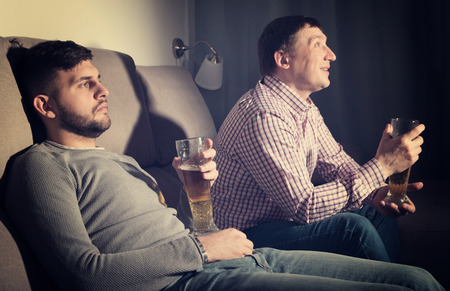 Indifferent guy sitting on sofa at home with glass of beer while friend emotionally watching tv