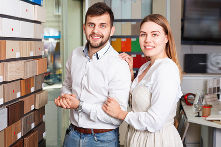 Young positive glad couple choosing material for furniture for their apartment in salon