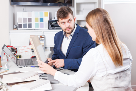Cheerful girl planning new furniture in her house in furniture salon
