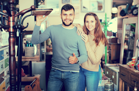 Portrait of attractive girl and her boyfriend in antique furnishings  showroom
