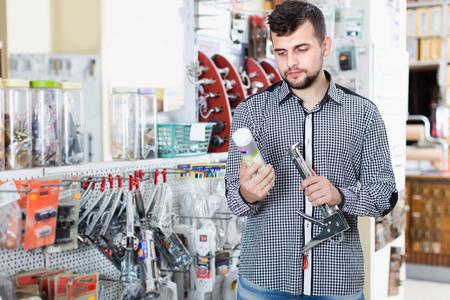 Smiling male choosing new glue in houseware shop Imagens
