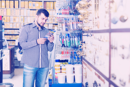 young man customer examining various glue tubes in houseware store