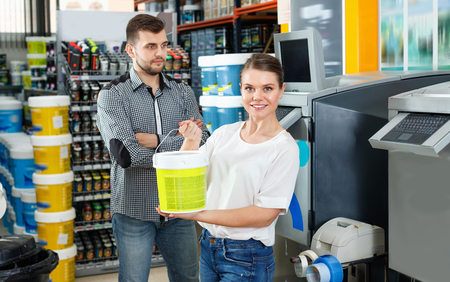 Young friendly pleasant woman standing near man and holding bucket of paint in household store Фото со стока