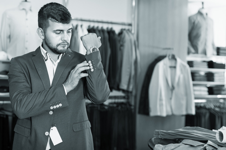 Adult male customer choosing jacket in men fashion store