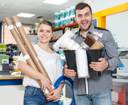 Active couple showing tools for house decoration in paint  store Reklamní fotografie