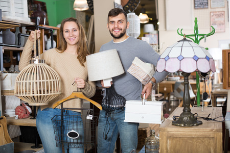 Portrait of happy young couple standing with purchases in furnishings salon
