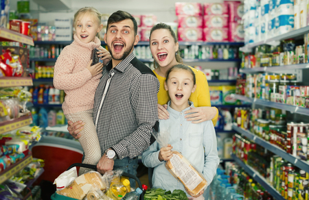 Cheerful marrieds with two daughters holding full basket after shopping in food store Foto de archivo