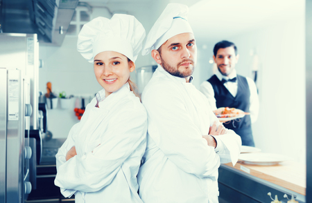 Portrait of professional cooks in kitchen on background of restaurant waiter with seafood dish