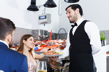Attractive girl asking waiter to cook fresh seafood from showcase in fish restaurant Stock Photo