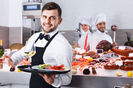 Cheerful bearded waiter standing with serving tray in fish restaurant