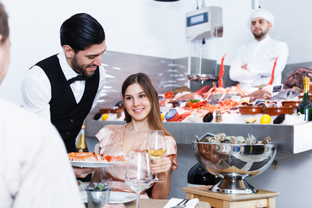Polite smiling young waiter bringing ordered seafood dishes to smiling couple at fish restaurant Stock Photo