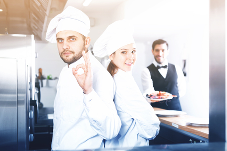 Two positive chefs in uniform in kitchen of fish restaurant on background of waiter with dish Фото со стока