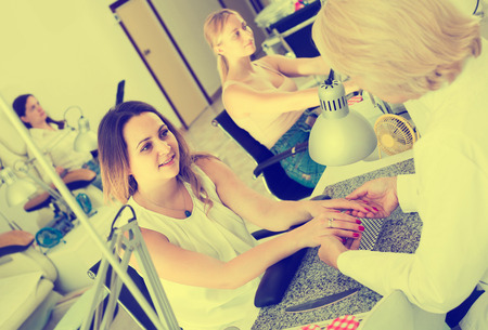 positive european female clients doing nails in nail salon in afternoon