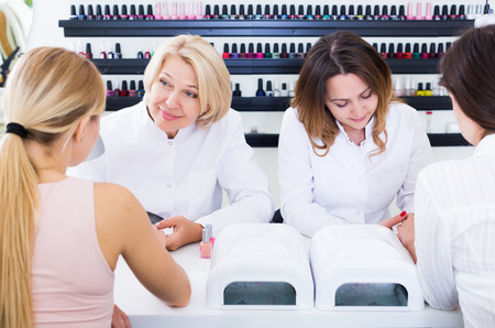 Two manicurists doing nails to clients in nail salon Zdjęcie Seryjne