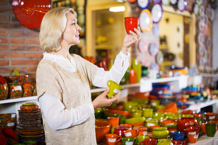 Portrait of elderly blonde female chooses ceramic ware in the cookware section at hypermarket