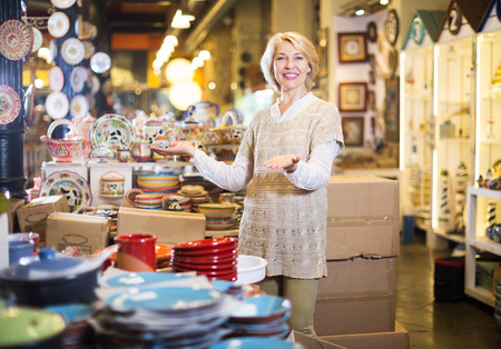 Mature glad blonde woman chooses ceramic ware in the cookware section at hypermarket