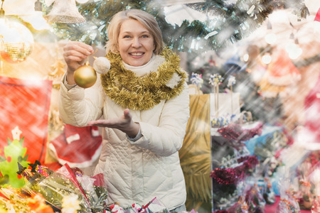 Mature woman seller with decorations at Christmas market outside