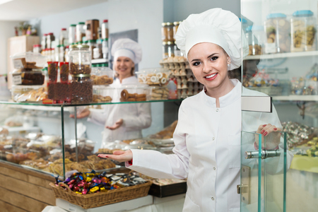 Beautiful female staff greeting clients in local confectionery Imagens