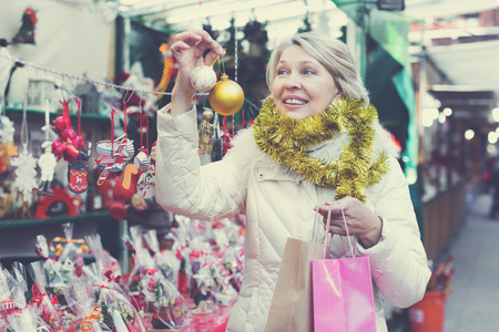 Smiling woman is buying toys for X-mas tree in the market outdoor. Stock Photo - 112714612