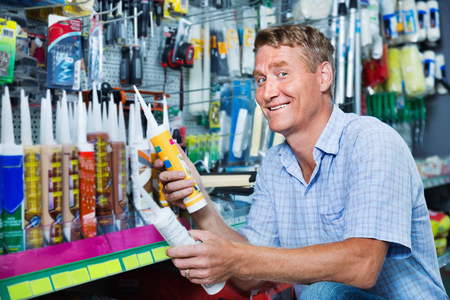 Portrait of positive male customer selecting sealant bottle in housewares department