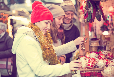 Cheerful family of three near the customer counter with Christmas decoration Stock Photo