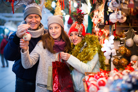 smiling family couple with teen daughter choosing Christmas decoration at fair