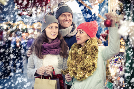friendly family couple with teen daughter choosing Christmas decoration at fair