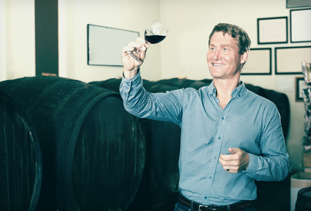 Portrait smiling man tasting wine before purchasing it in wine cellar 写真素材 - 112716363