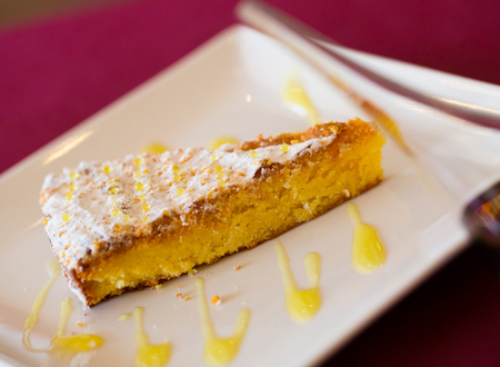 Delicious almond pie Tarta de Santiago served with orange sauce on white plate